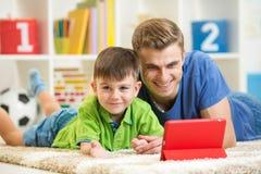 Père heureux et son enfant avec le PC de comprimé images stock