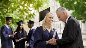 Père heureux félicitant la fille licenciée tenant ses mains près de l'université photographie stock libre de droits
