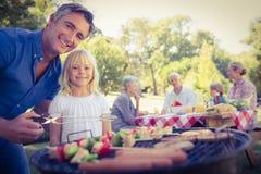 Père heureux faisant le barbecue avec sa fille image stock