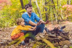 Père heureux faisant le barbecue avec son fils un jour d'automne Photo stock