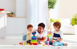 Père heureux jouant avec des fils à la maison image stock