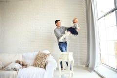 Père heureux jouant avec sa fille de bébé dans la vie lumineuse Photographie stock libre de droits