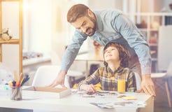 Père heureux joyeux se tenant derrière son fils Photographie stock