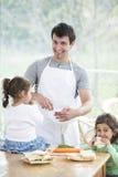 Père heureux préparant la nourriture avec de petites filles à la maison Photo libre de droits