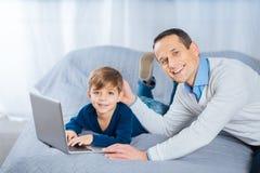 Père heureux tapotant le chef de son fils causant en ligne Photographie stock libre de droits