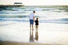 Père heureux tenant tenir la main du petit fils marchant ensemble sur la plage avec nu-pieds Photos stock