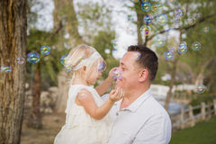 Père Holding Baby Girl appréciant des bulles dehors au parc Photographie stock