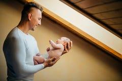 Père Holding Newborn Baby à la maison près de fenêtre photos stock
