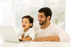Père indien d'ordinateur portable de garçon image libre de droits