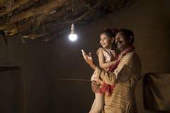 Père indien rural avec la fille ravie sur l'électricité atteignant leur maison photo libre de droits