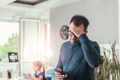 Père inquiété regardant le téléphone intelligent Image stock