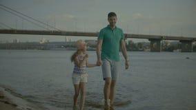 Père insouciant et fille marchant sur la plage banque de vidéos