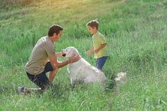 Père insouciant et fils ayant l'amusement avec Labrador Photo libre de droits