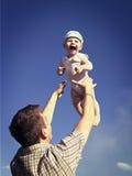 Père jetant le bébé en l'air dans le ciel Images libres de droits
