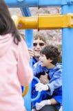 Père jouant à la cour de jeu avec le fils handicapé Image stock