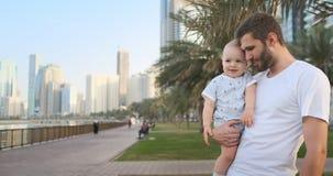 Père jouant avec des fils pendant l'été dans une ville moderne le tenant et étreignant la position dans un T-shirt blanc et des s banque de vidéos