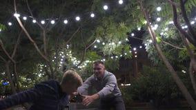 Père jouant avec le fils dans la cour décorée pour la nouvelle année, les vacances et l'enfance banque de vidéos