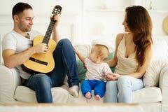 Père jouant la guitare pour la mère et le fils loisirs photographie stock
