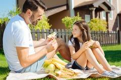 Père joyeux et fille tenant des sandwichs sur le pique-nique Photo stock