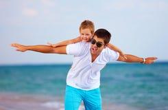 Père joyeux et fils ayant l'amusement sur la plage Photos stock