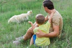 Père joyeux passant le temps avec l'enfant sur le pré Photos libres de droits