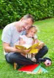 Père lisant un livre à sa fille Photo stock