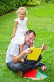 Père lisant un livre à sa fille Photos libres de droits