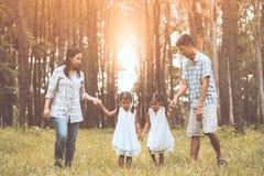 Père, mère et deux filles de petit enfant tenant la main Photographie stock libre de droits