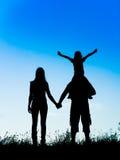 Père, mère et fille de silhouette Photographie stock