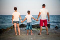 Père, mère et fils jugeant des mains tournées de retour Images libres de droits