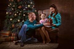 Père, mère et leur fille près d'un arbre de Noël Image libre de droits
