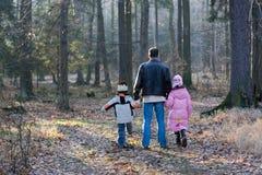 Père marchant avec des enfants dans la forêt   Photographie stock libre de droits