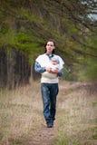Père marchant avec le descendant dans l'élingue photo libre de droits