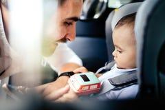 Père mettant le bébé d'un an dans le siège et le sourire de voiture d'enfant Mode de vie, concept de transport photos libres de droits