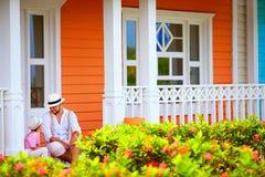 Père mignon et fils s'asseyant et parlant sur le porche, rue des Caraïbes image libre de droits