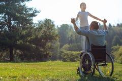 père Mobilité-altéré tenant sa fille sur le recouvrement Image stock