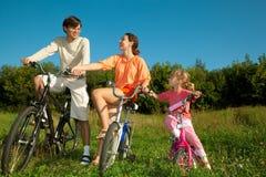 Père, momie et descendant sur des bicyclettes en stationnement Photos libres de droits