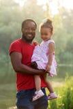 Père noir étreignant la fille de bébé au coucher du soleil Images stock
