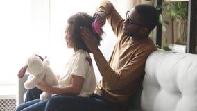 Père noir aimant faisant les cheveux Afro de brossage de la fille d'enfant banque de vidéos