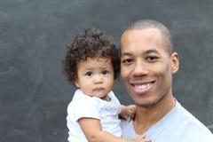 Père noir heureux et petit descendant mignon embrassant, souriant photo stock