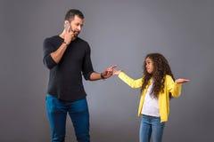Père noir parlant au téléphone tandis que sa fille regardant le questio Images libres de droits