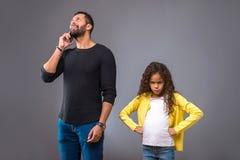 Père noir parlant au téléphone tandis que sa fille semblant fâchée photos libres de droits