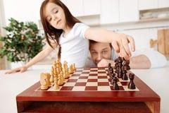 Père observant sa fille déplacer un chevalier Image stock