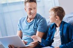 Père optimiste et fils parlant du projet d'école Photo libre de droits