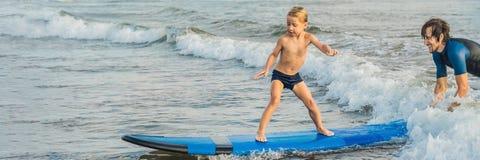 Père ou instructeur enseignant à ses 4 le fils an comment surfer en mer des vacances ou des vacances Voyage et sports avec photographie stock libre de droits