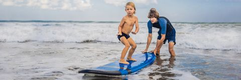 Père ou instructeur enseignant à ses 4 le fils an comment surfer en mer des vacances ou des vacances Voyage et sports avec photos libres de droits