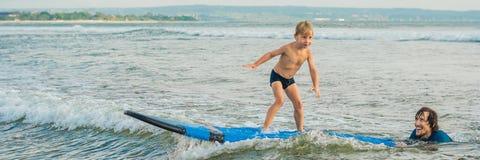 Père ou instructeur enseignant à ses 4 le fils an comment surfer en mer des vacances ou des vacances Voyage et sports avec photo stock
