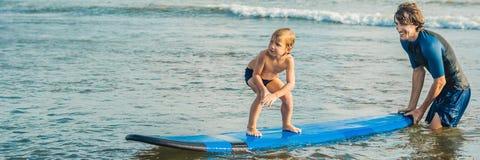 Père ou instructeur enseignant à ses 4 le fils an comment surfer en mer des vacances ou des vacances Voyage et sports avec image stock