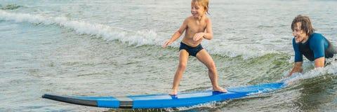Père ou instructeur enseignant à ses 4 le fils an comment surfer en mer des vacances ou des vacances Voyage et sports avec photographie stock