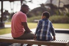 Père parlant au fils près du côté de piscine Image libre de droits